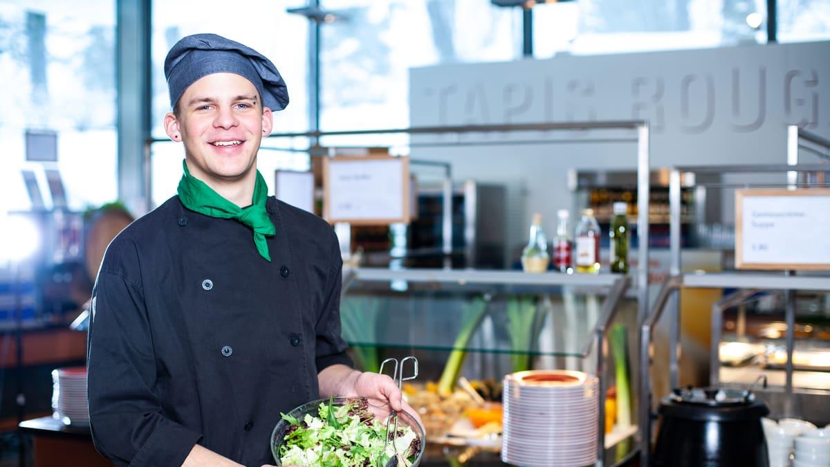 Lernender Systemgastronomiefachmann hält eine Schüssel voller Salat