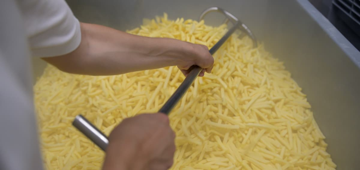Person mischt geschnittene Kartoffeln