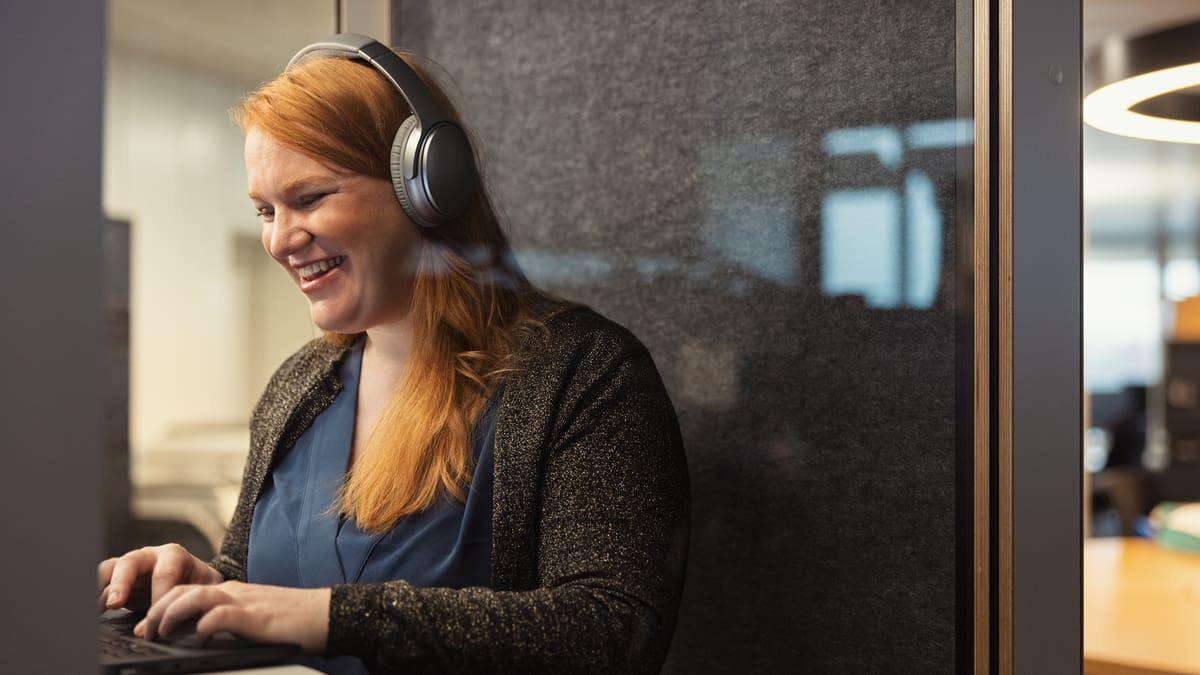 Frau in Telefonkabine mit Kopfhörer