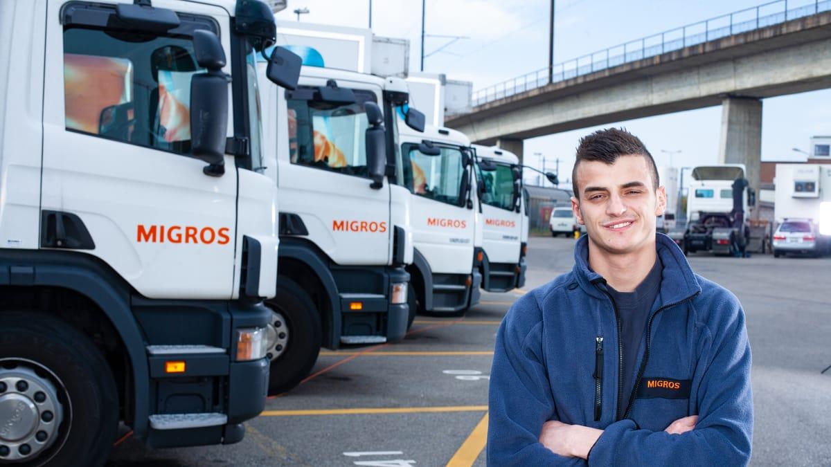 Lernender Strassentransportfachmann steht vor dem Lastwagenparkplatz