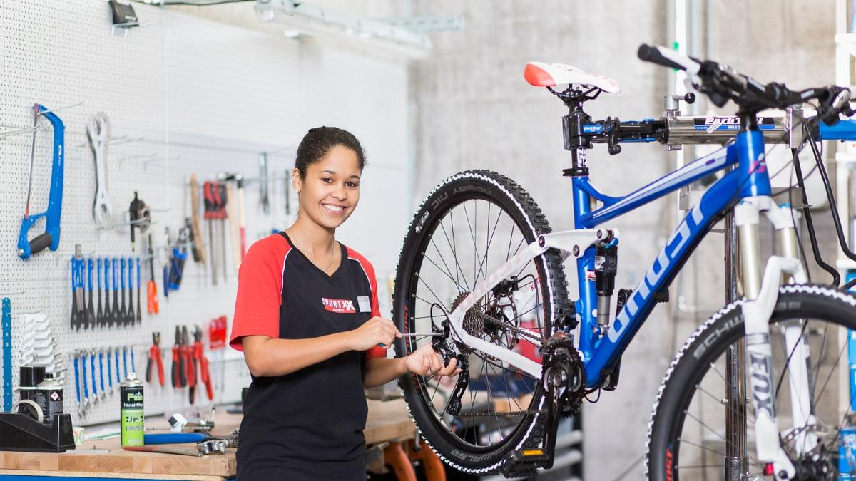 Lernende Fahrradmechanikerin schraubt an einem Fahrrad
