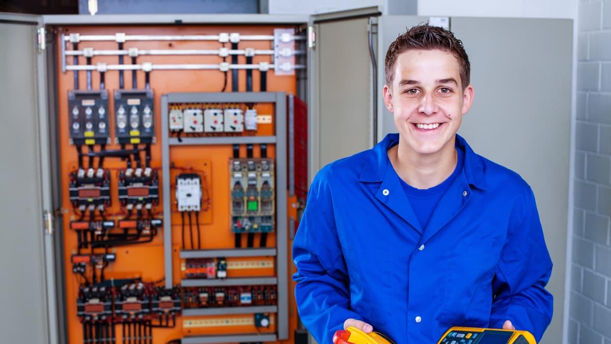 Lernender Elektroinstallateur hält Messgeräte in der Hand