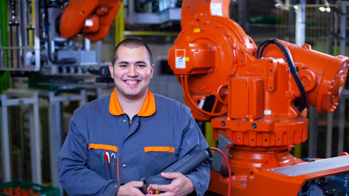 Lernender Anlageführer hält ein Maschinensteuergerät in der Hand