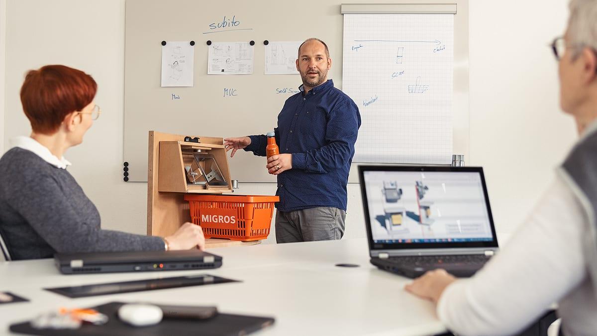 Drei Personen mit Prototyp eines Self Check-Out Systems in Sitzungszimmer