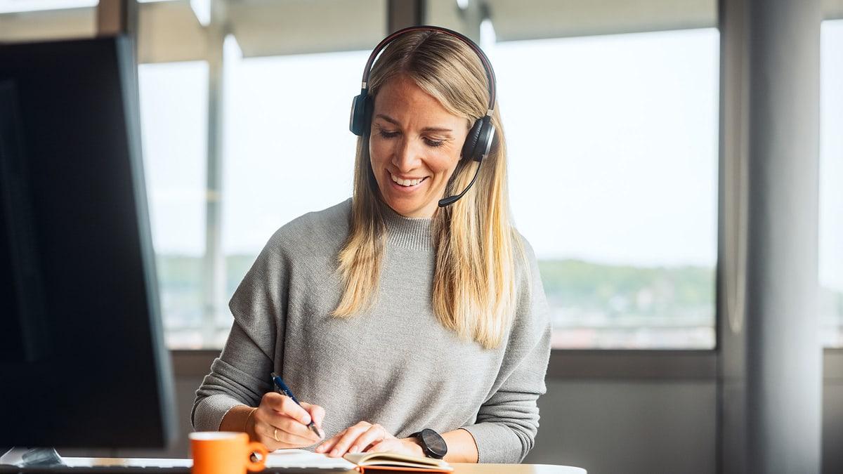 Frau mit Headset an Arbeitsplatz
