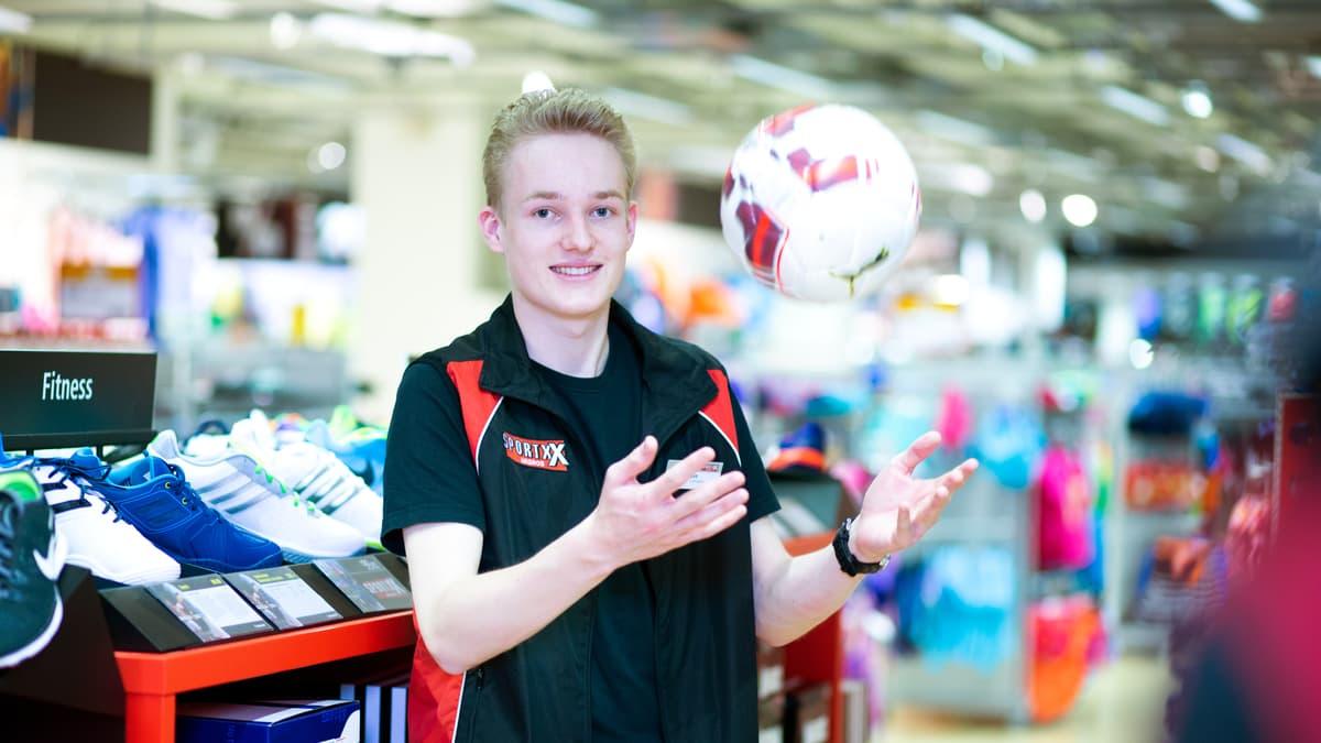 Lernender Detailhandelsfachmann (Sportartikel) schmeisst einen Ball in die Luft