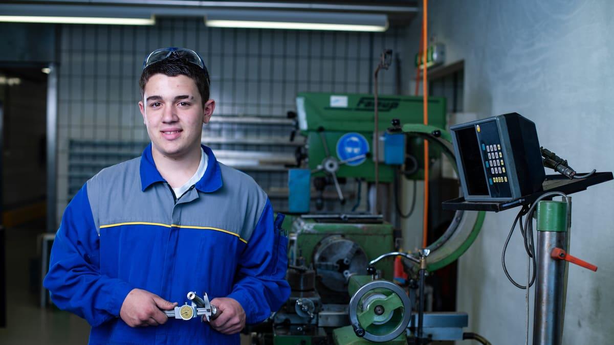 Lernender Produktionsmechaniker misst den Durchmesser einer Eisenstange