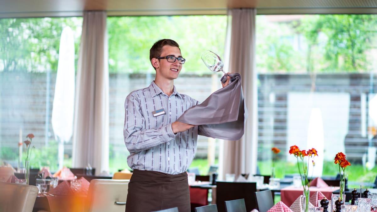 Lernender Restaurationsfachmann prüft Sauberkeit beim Weinglas