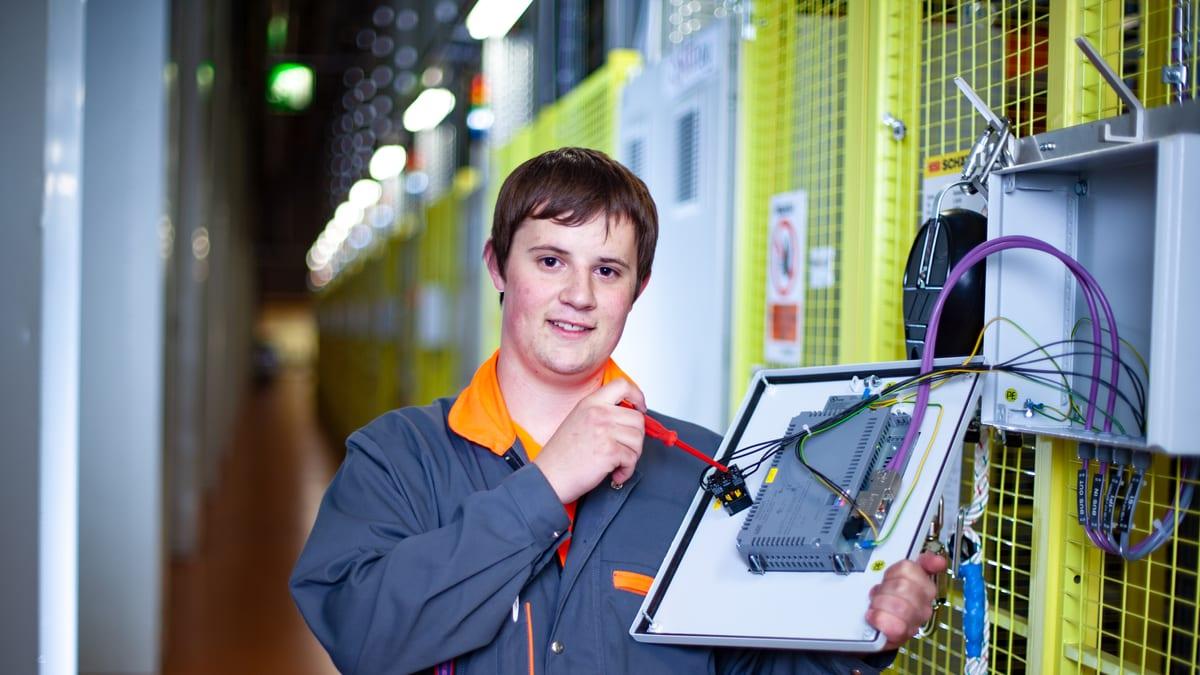 Lernender Automatikmonteur schraubt an der Anlage