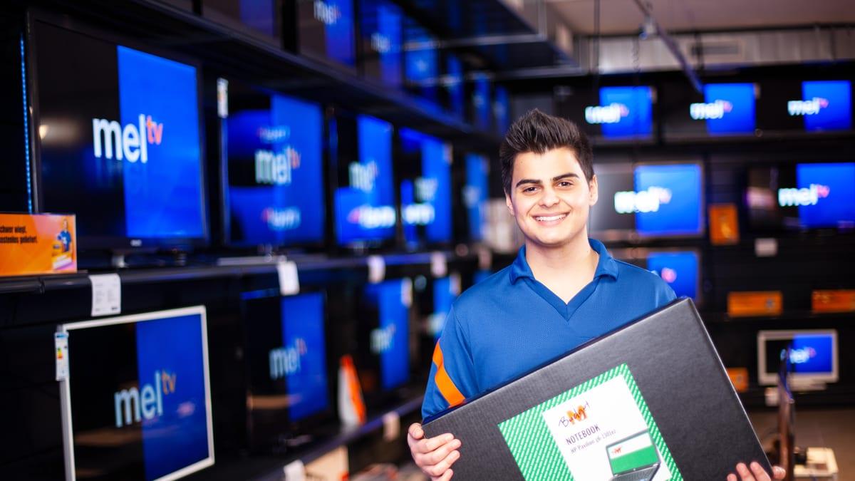 Lernender Detailhandelsfachmann (Consumer-Electronics) hält ein Notebook