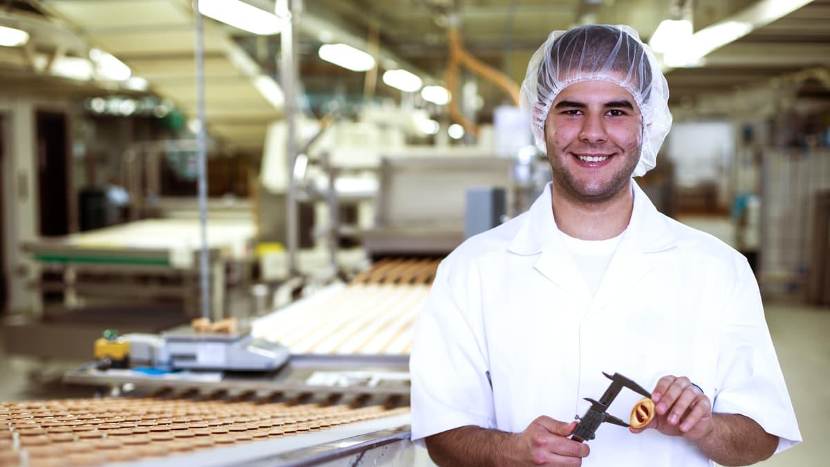 Lernender Lebensmitteltechnologe misst die Grösse eines Keks