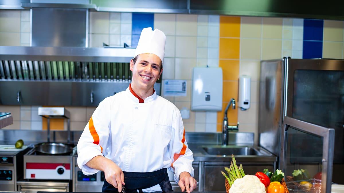 Lernender Küchenangestellter brät Gemüse an