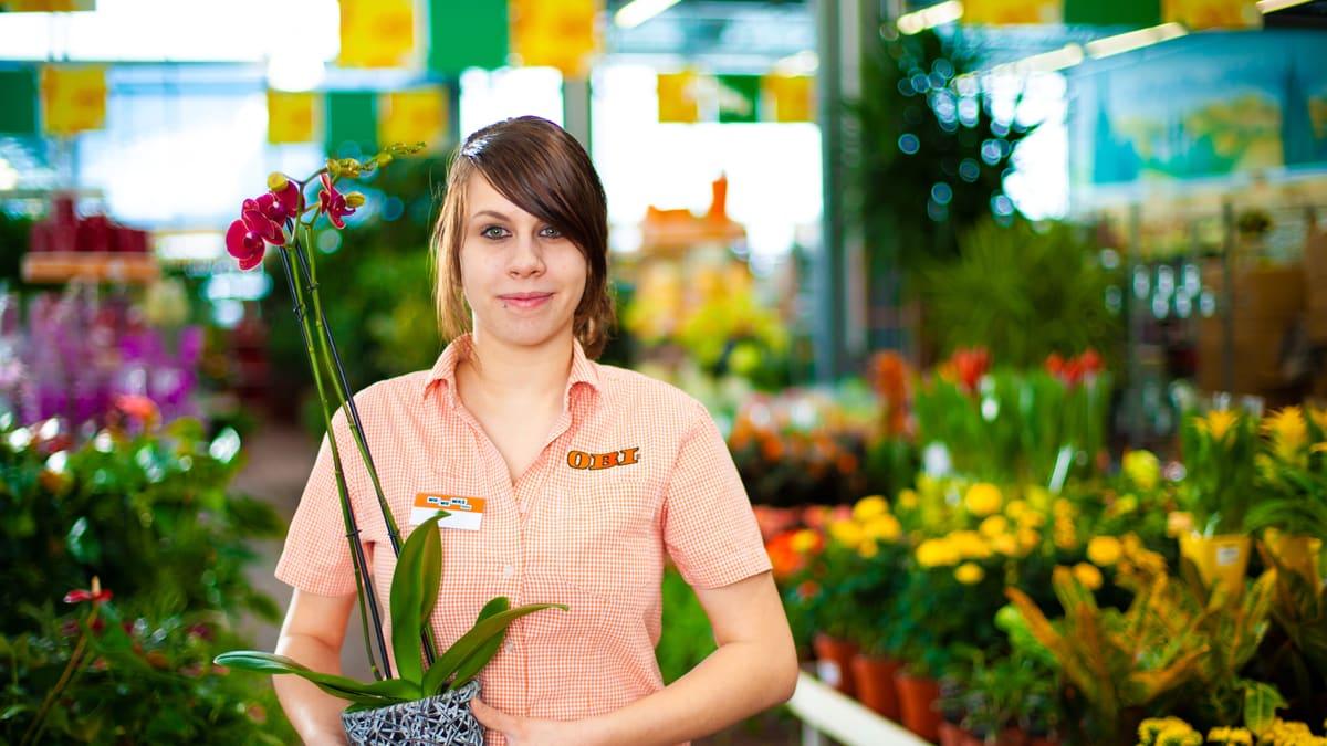 Lernende Detailhandelsfachfrau (Garden) hält Orchidee im Topf