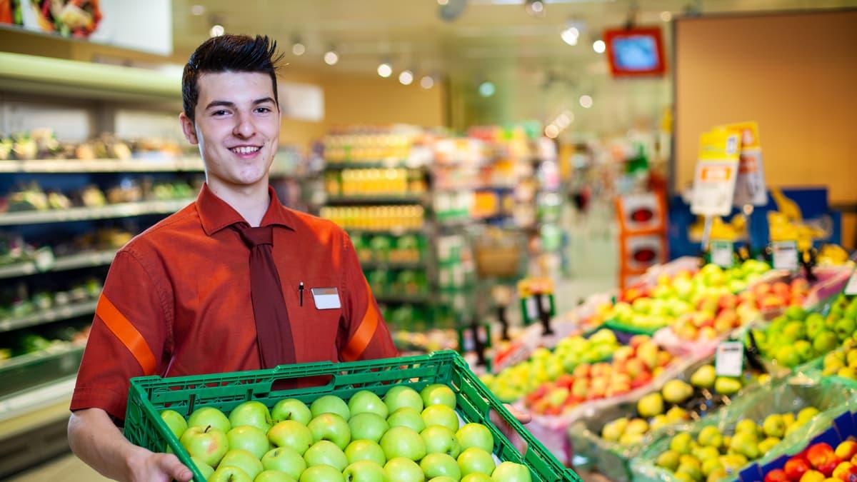 Lernender Detailhandelsfachmann (Nahrungs-und Genussmittel) hält einen Korb mit Äpfeln