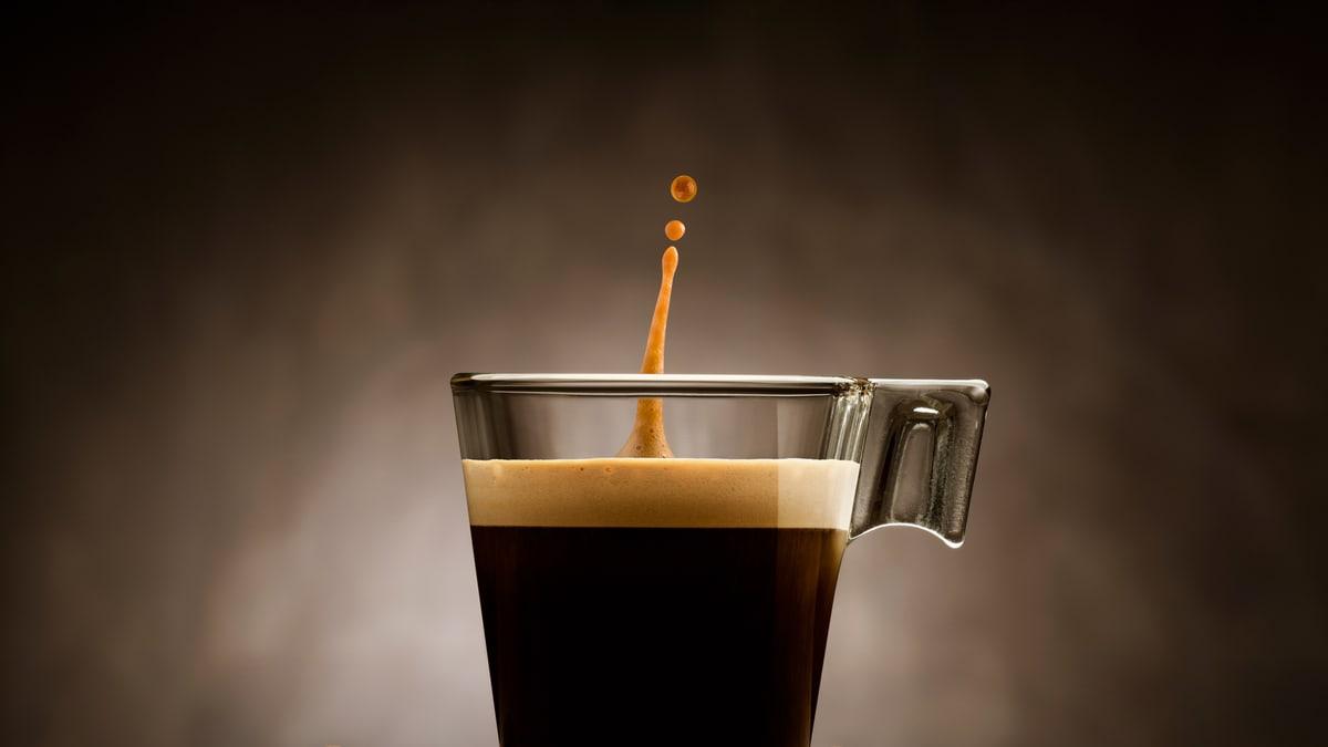Kaffee im Glas mit Spritzer