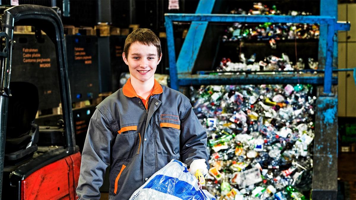 Lernender Recyclist hält einen Plasticksack für Petflaschen