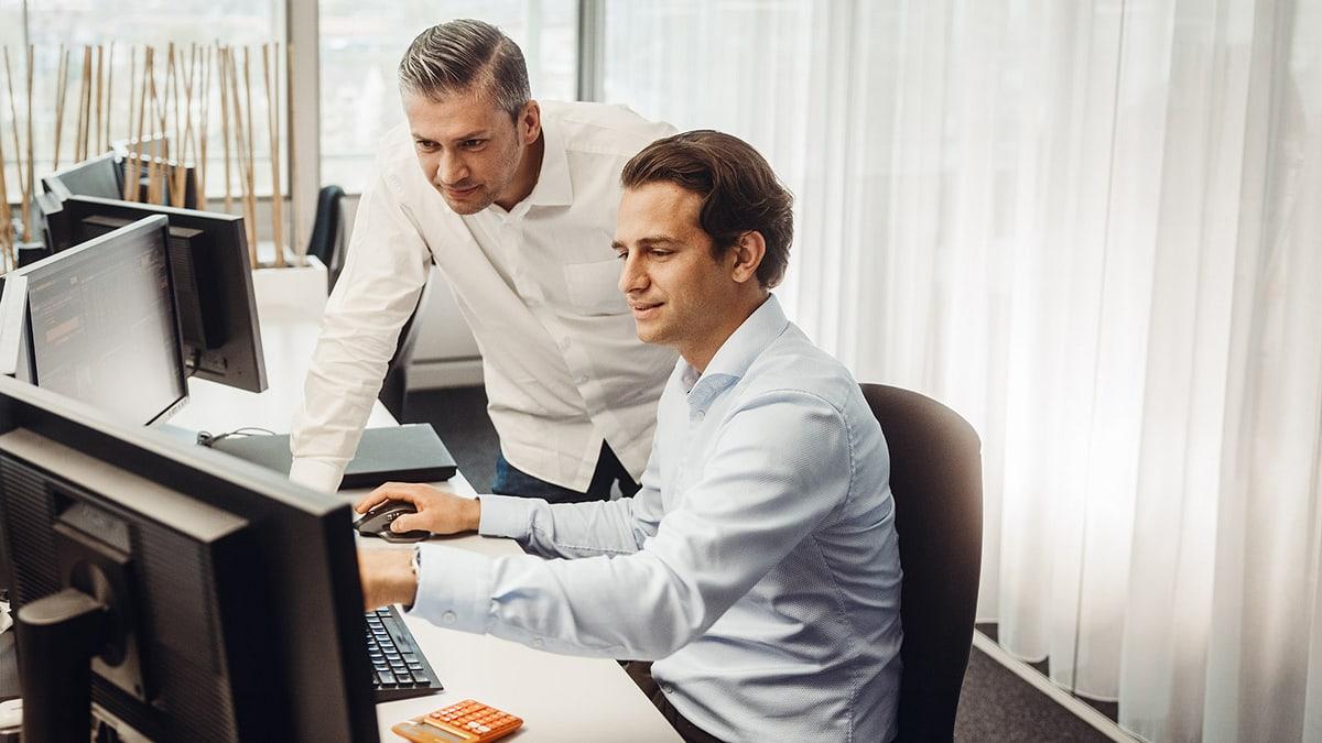 Zwei Personen im Gespräch am Arbeitsplatz