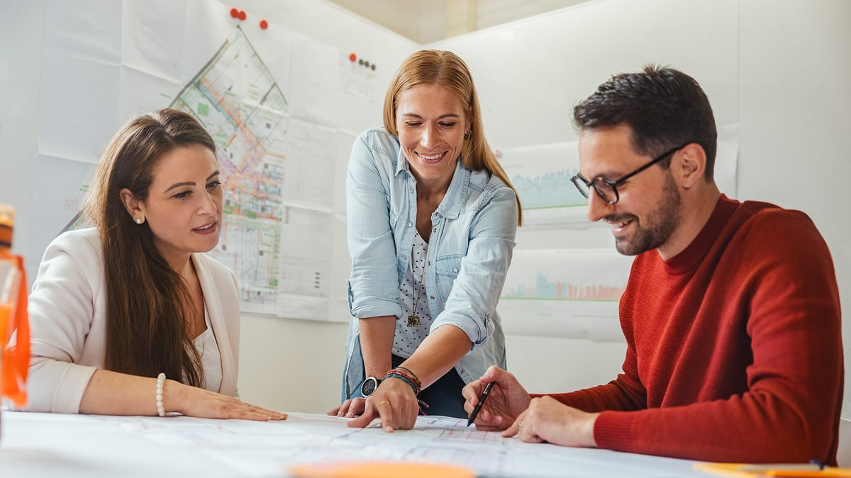 Drei Personen besprechen Pläne im Sitzungszimmer